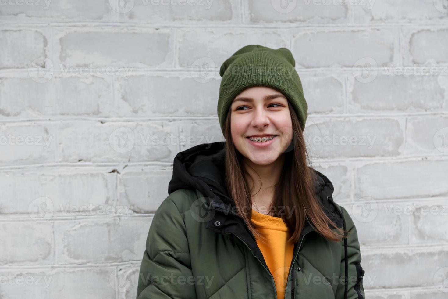 Portrait d'une belle jeune fille souriante avec des accolades dans un pull jaune et un chapeau kaki photo