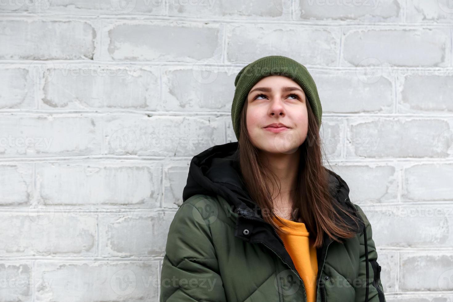 Portrait d'une belle fille pensive dans un pull jaune et un chapeau kaki photo