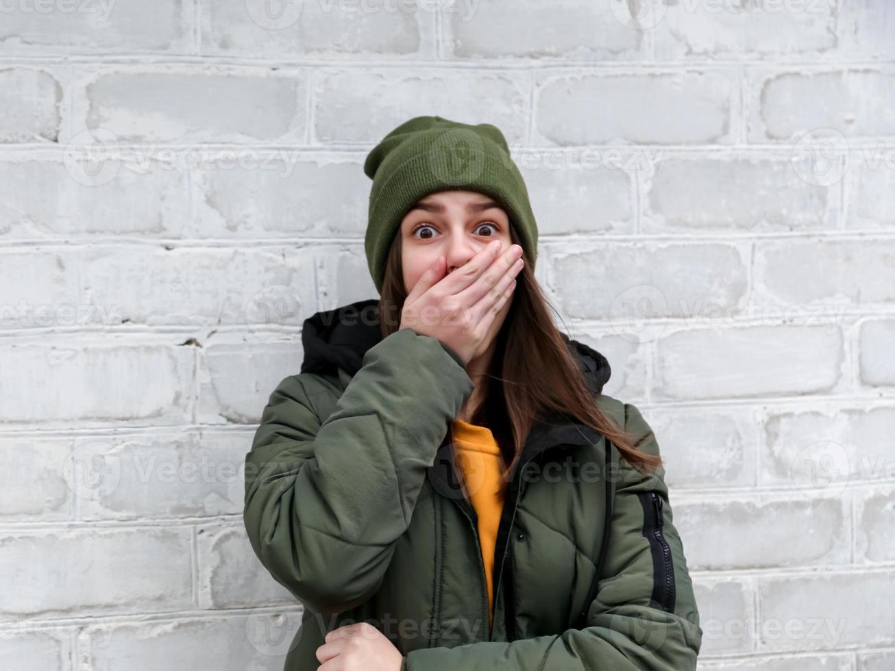 Portrait d'une belle fille choquée qui ferme la bouche avec sa main dans un pull jaune et un chapeau kaki qui se tient près d'un mur de briques blanches photo