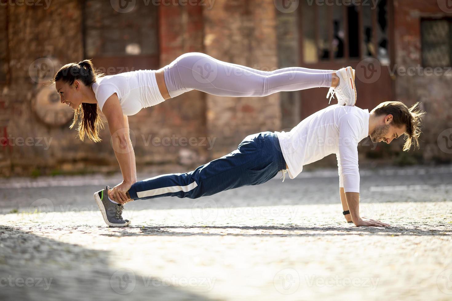 jeune couple faisant deux exercice push up en milieu urbain photo