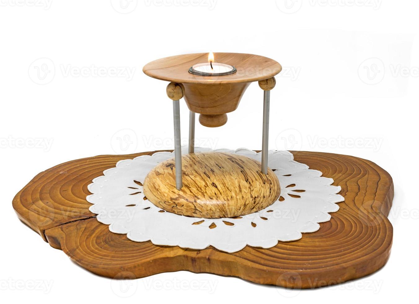 Bougeoir en bois en plusieurs parties avec bougie allumée se dresse sur une planche de bois sombre photo