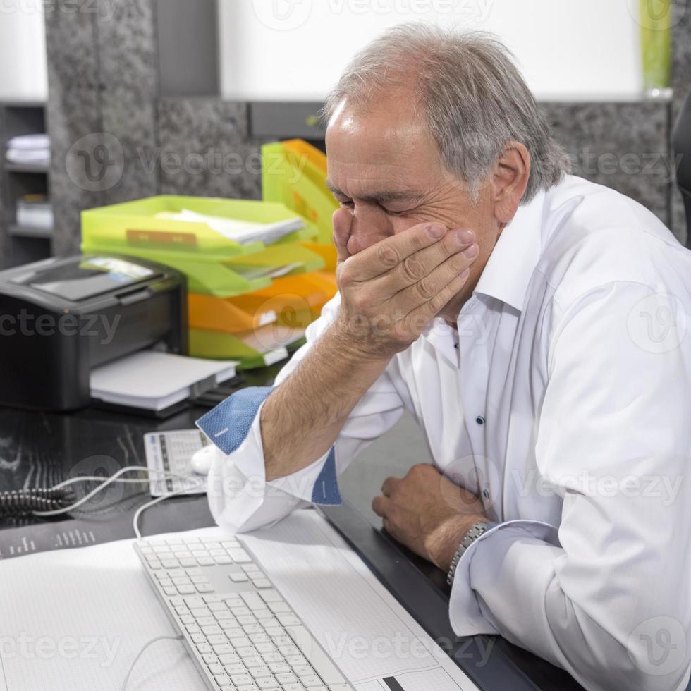 homme âgé assis désespérément à un bureau photo