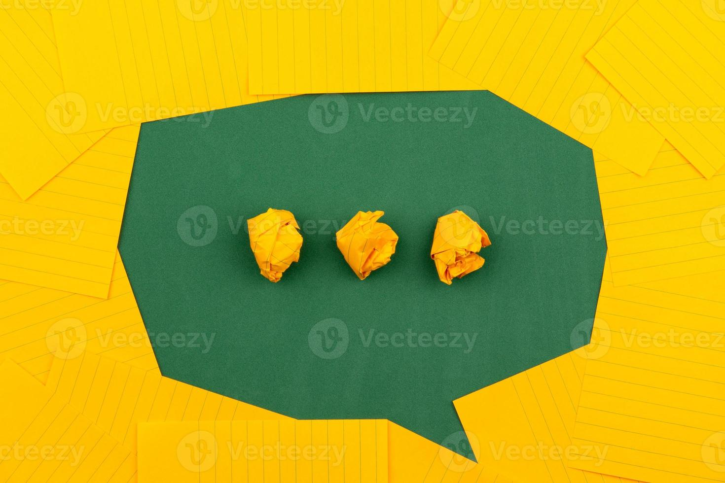 Des feuilles de papier orange sur une commission scolaire verte forment une bulle de discussion photo