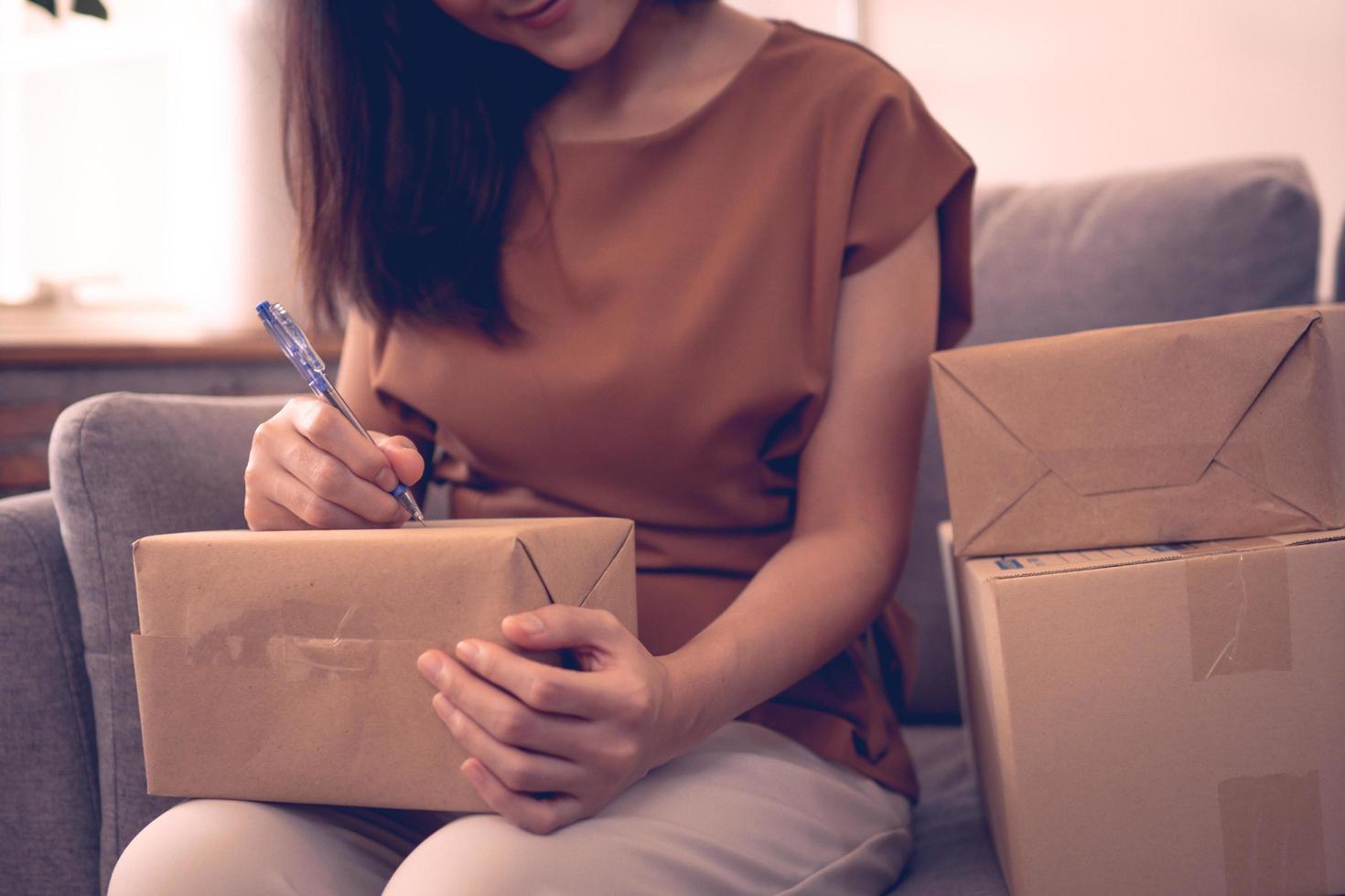 Gros plan de la main de la femme écrit sur la boîte de colis se préparant à la livraison en ligne entreprise concept photo