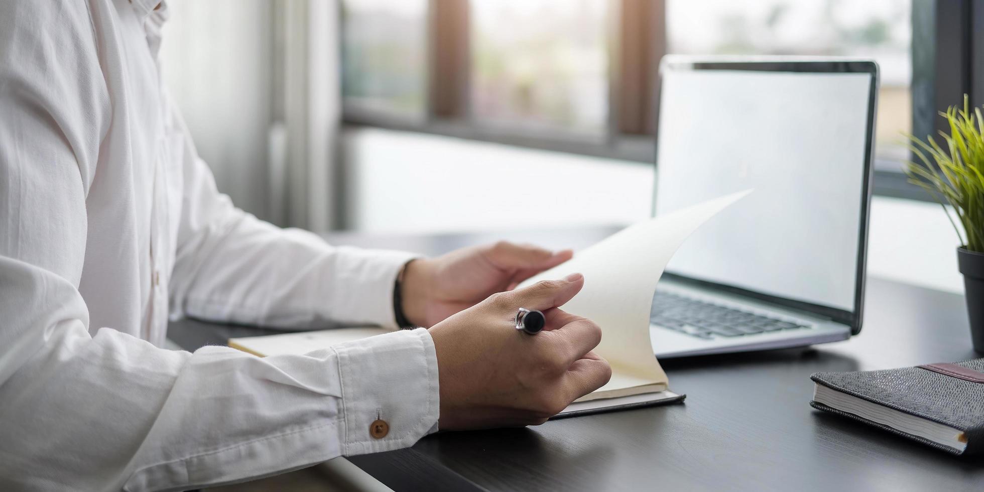 Business planning business man writing on notebook et travaillant sur ordinateur portable dans un bureau moderne homme étudiant cours en ligne via ordinateur portable et conférence sur le bloc-notes photo