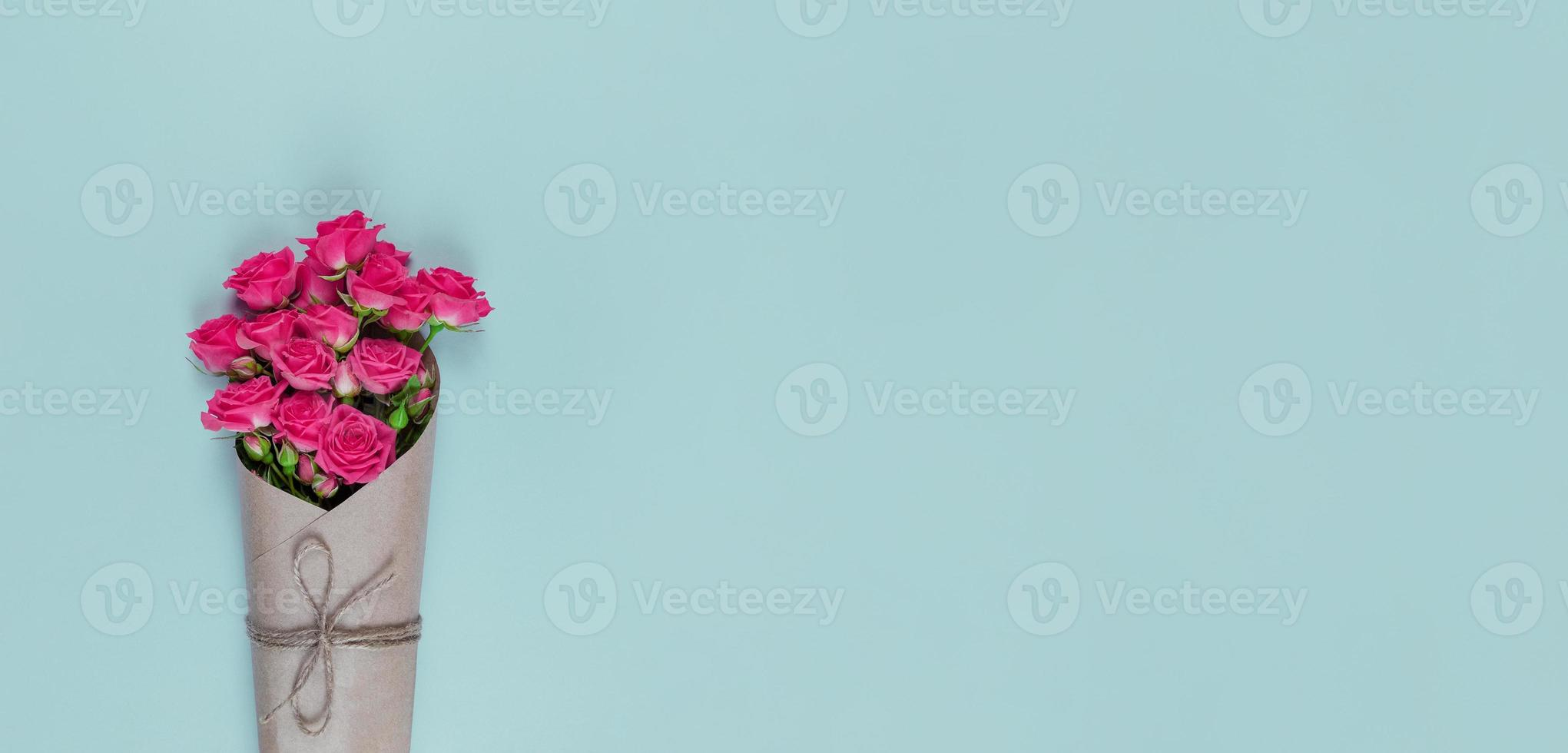 Bouquet de petites roses roses à fleurs enveloppées dans du papier craft sur fond bleu with copy space photo