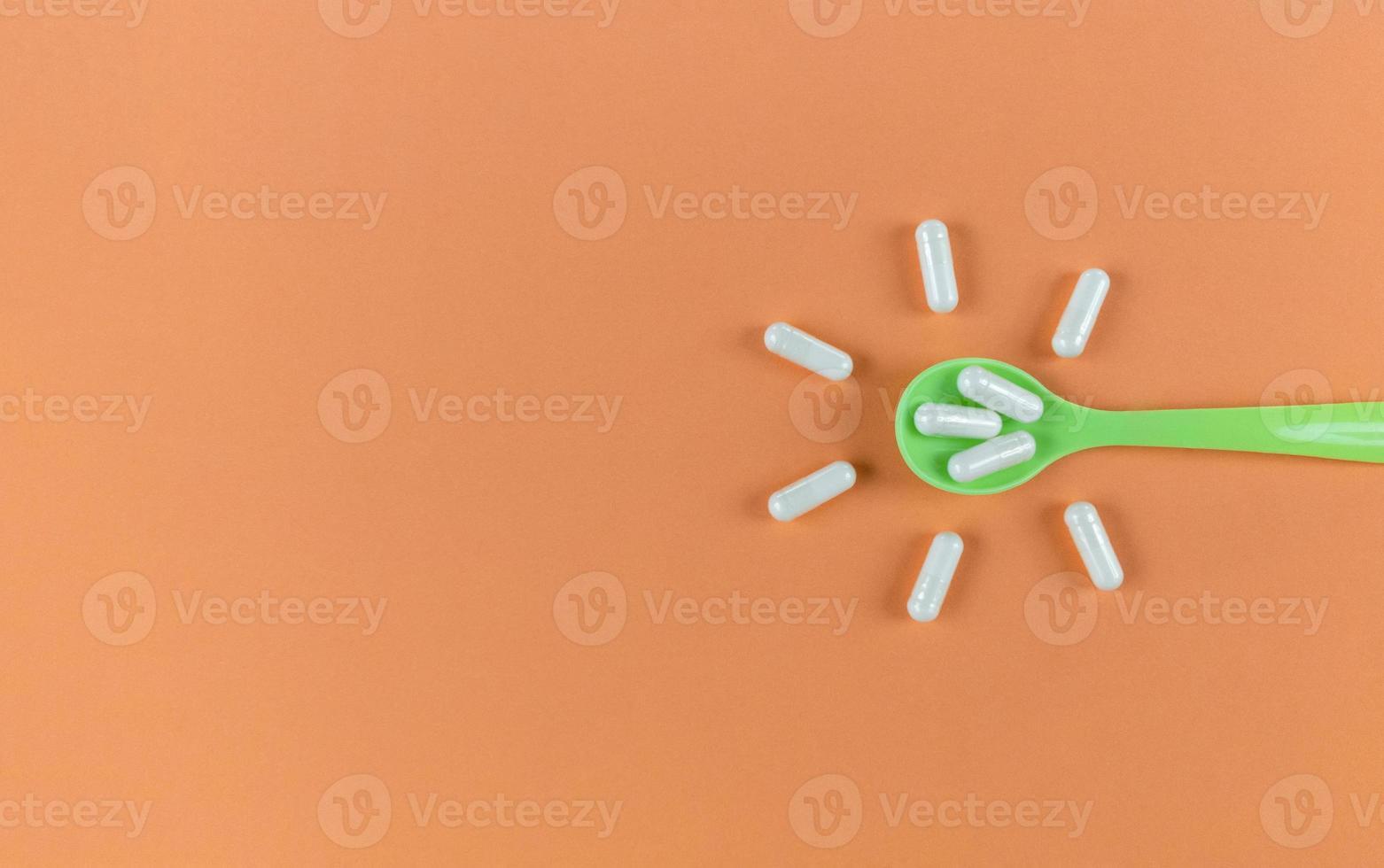 cuillère verte et capsules blanches sur fond orange avec espace de copie photo