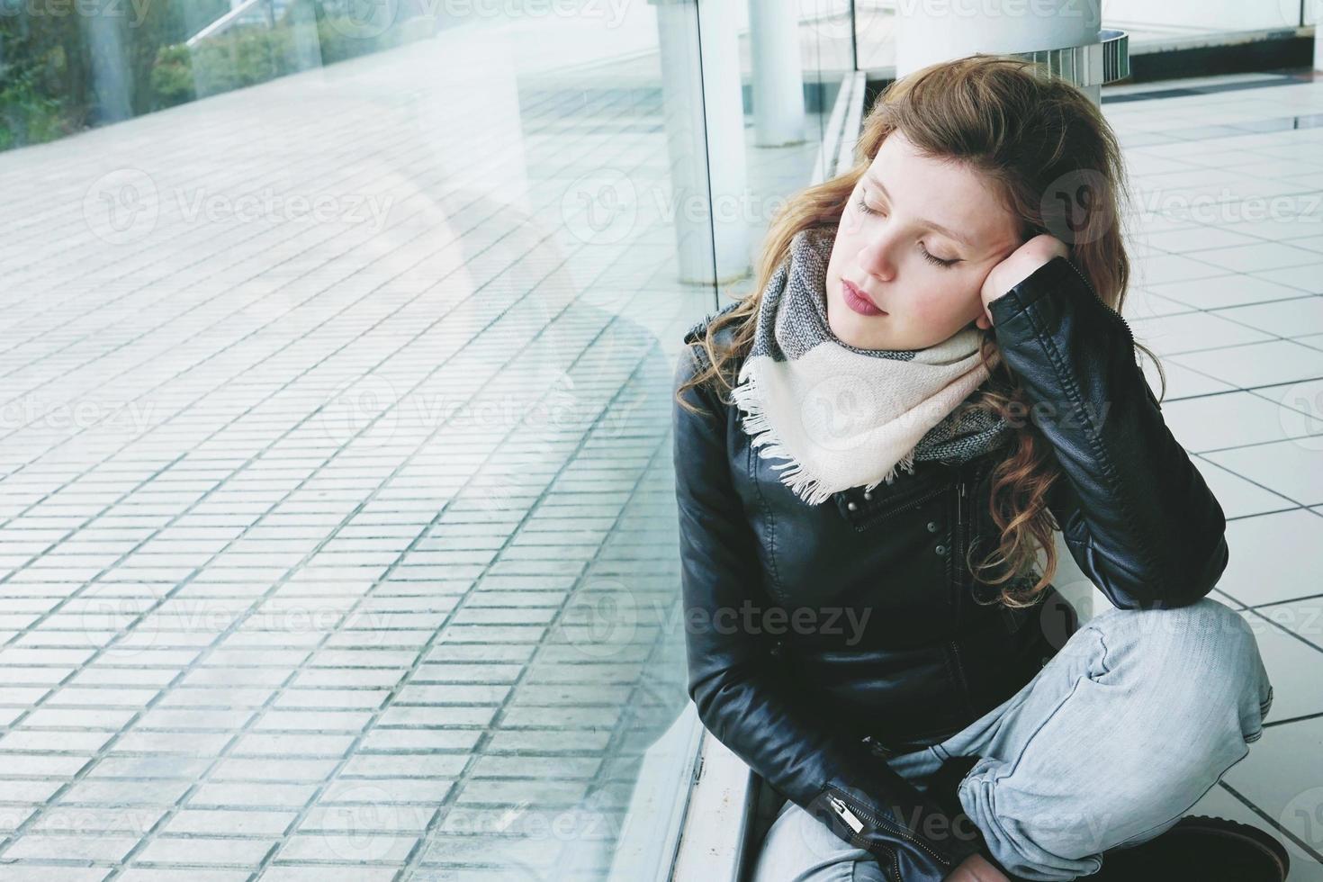 belle jeune femme reflétée dans une immense fenêtre photo