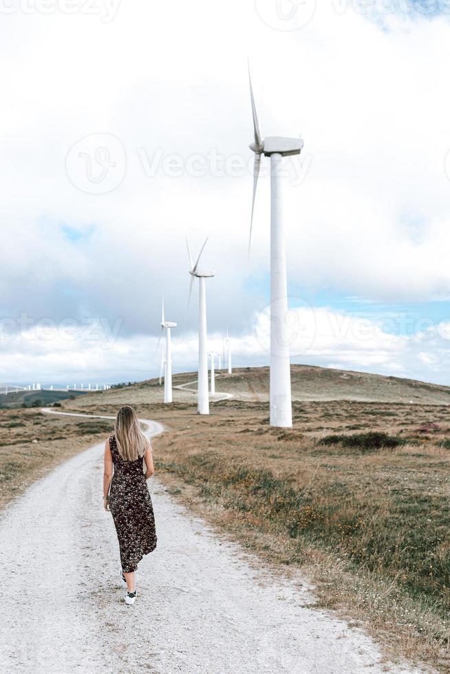 Femme marchant près d'une ferme éolienne photo