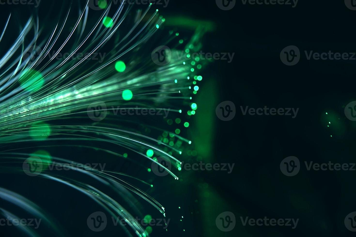 une macro étonnante et vibrante de tuyaux optiques en fibre verte qui illuminent en faisant des étincelles et des paillettes avec un fond noir photo