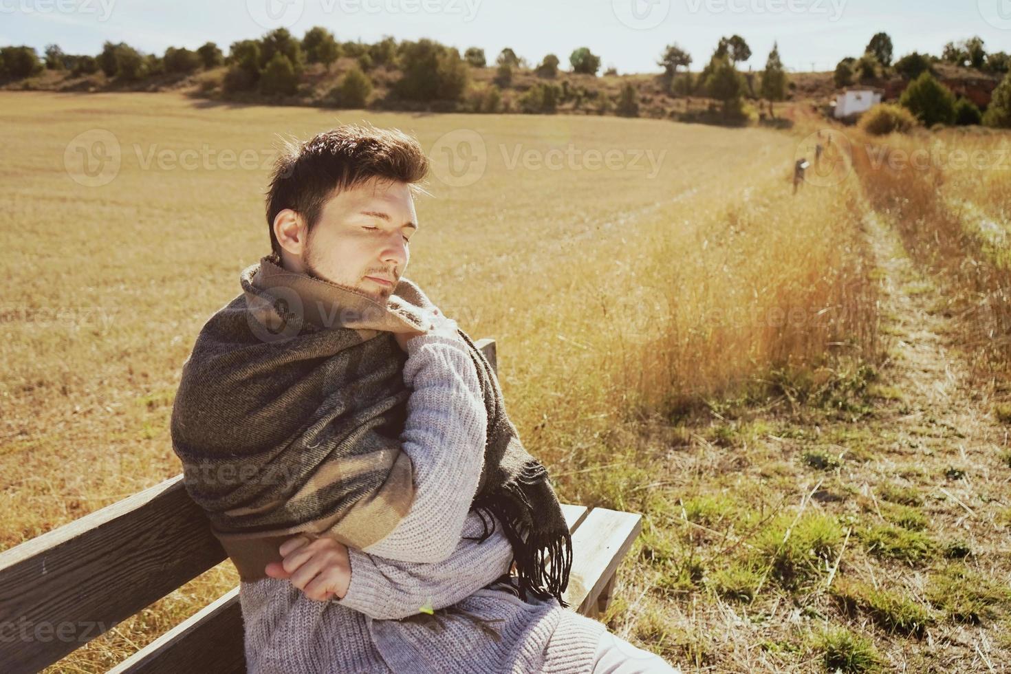 Un jeune homme avec une écharpe chaude profitant au calme du soleil d'automne du matin dans un champ jaune avec le contre-jour du ciel bleu photo
