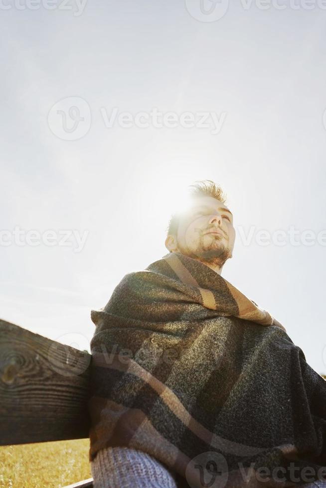 Jeune homme profitant du calme soleil d'automne matin avec la lueur du rétroéclairage du ciel bleu photo