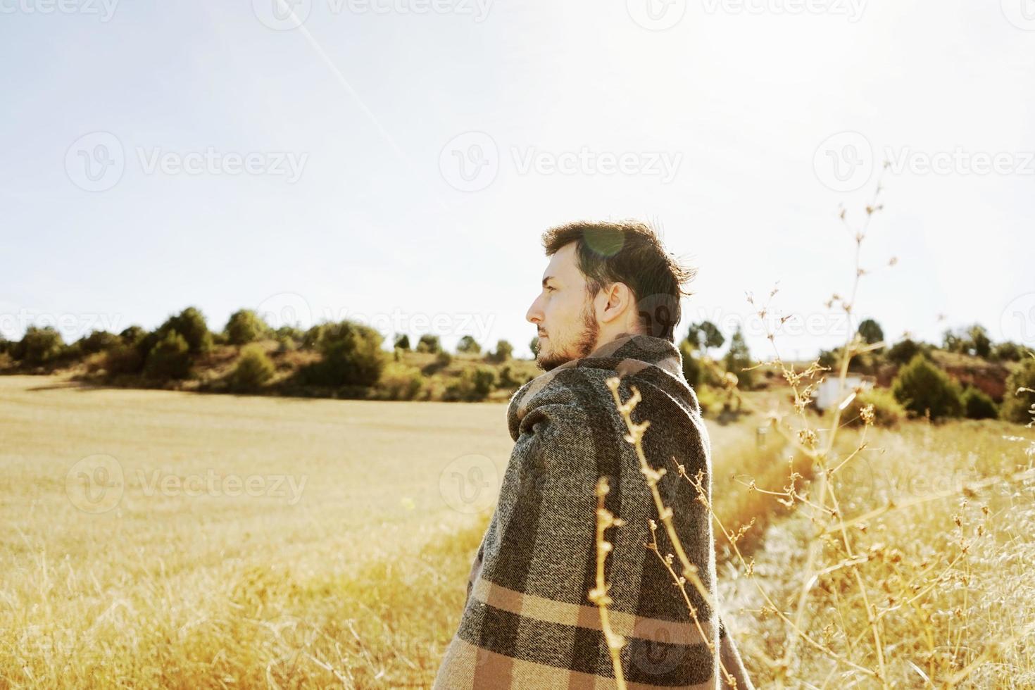 Côté d'un stand jeune homme profitant dans le calme du soleil d'automne du matin dans un chemin d'un champ jaune avec le contre-jour du ciel bleu photo