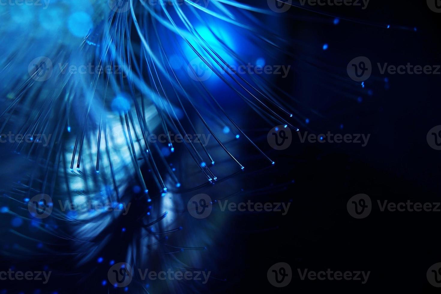 une macro étonnante et vibrante de tuyaux optiques en fibre bleue qui illuminent en faisant des étincelles et des paillettes avec un fond noir photo