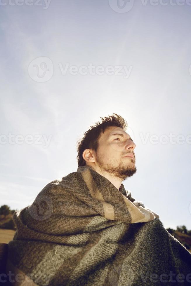 Face latérale d'un jeune homme avec une écharpe chaude profitant au calme du soleil d'automne du matin avec le contre-jour du ciel bleu photo