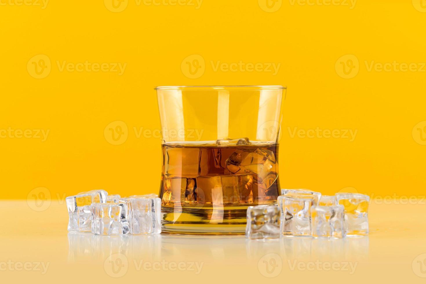 verre de whisky avec des glaçons sur fond jaune photo