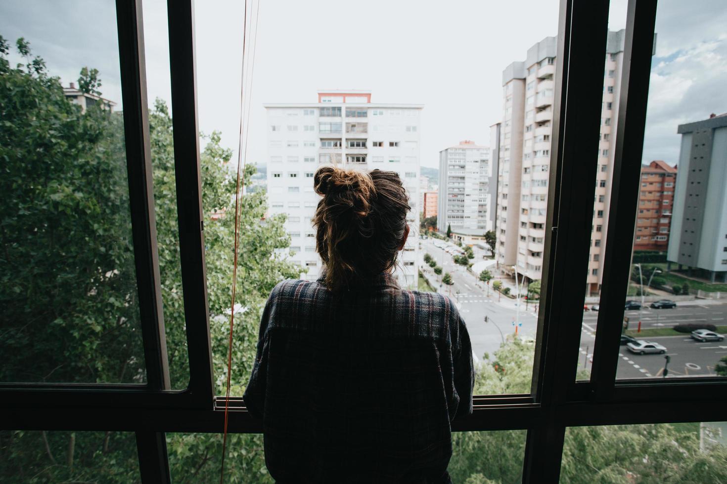 Femme inquiète à la fenêtre de la ville pendant une journée de printemps photo