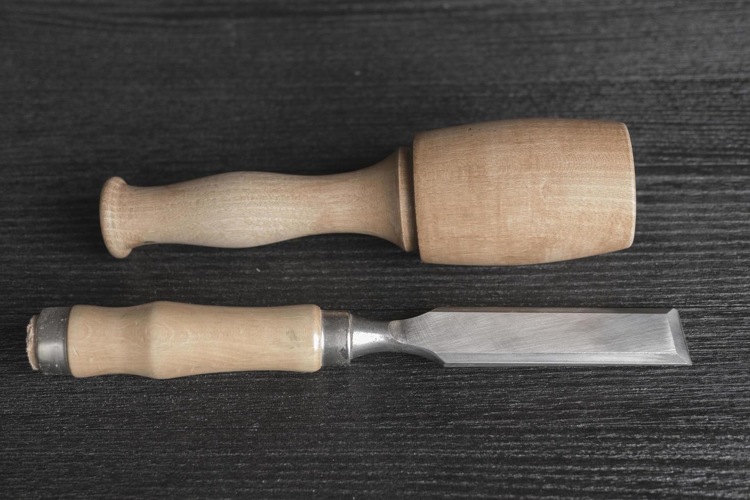 Ciseau et maillet en bois sur fond noir atelier de menuisier photo