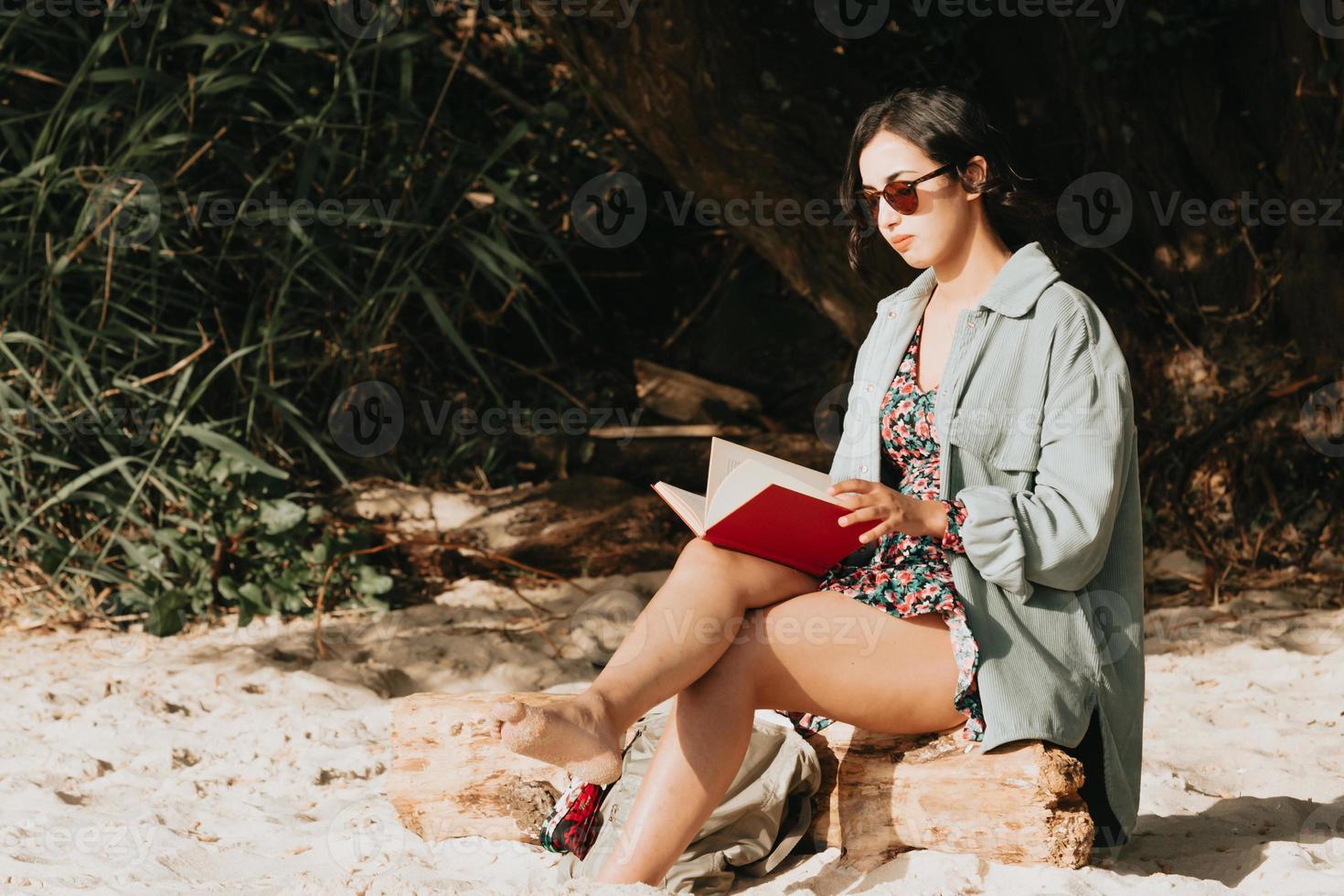 Jeune femme marocaine en vêtements modernes assis sur la plage en lisant un livre photo