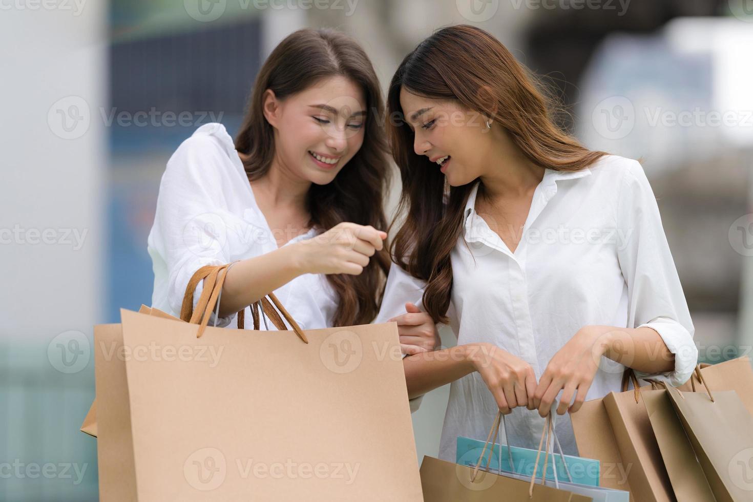 Happy friends shopping deux jeunes femmes tiennent des sacs à provisions photo