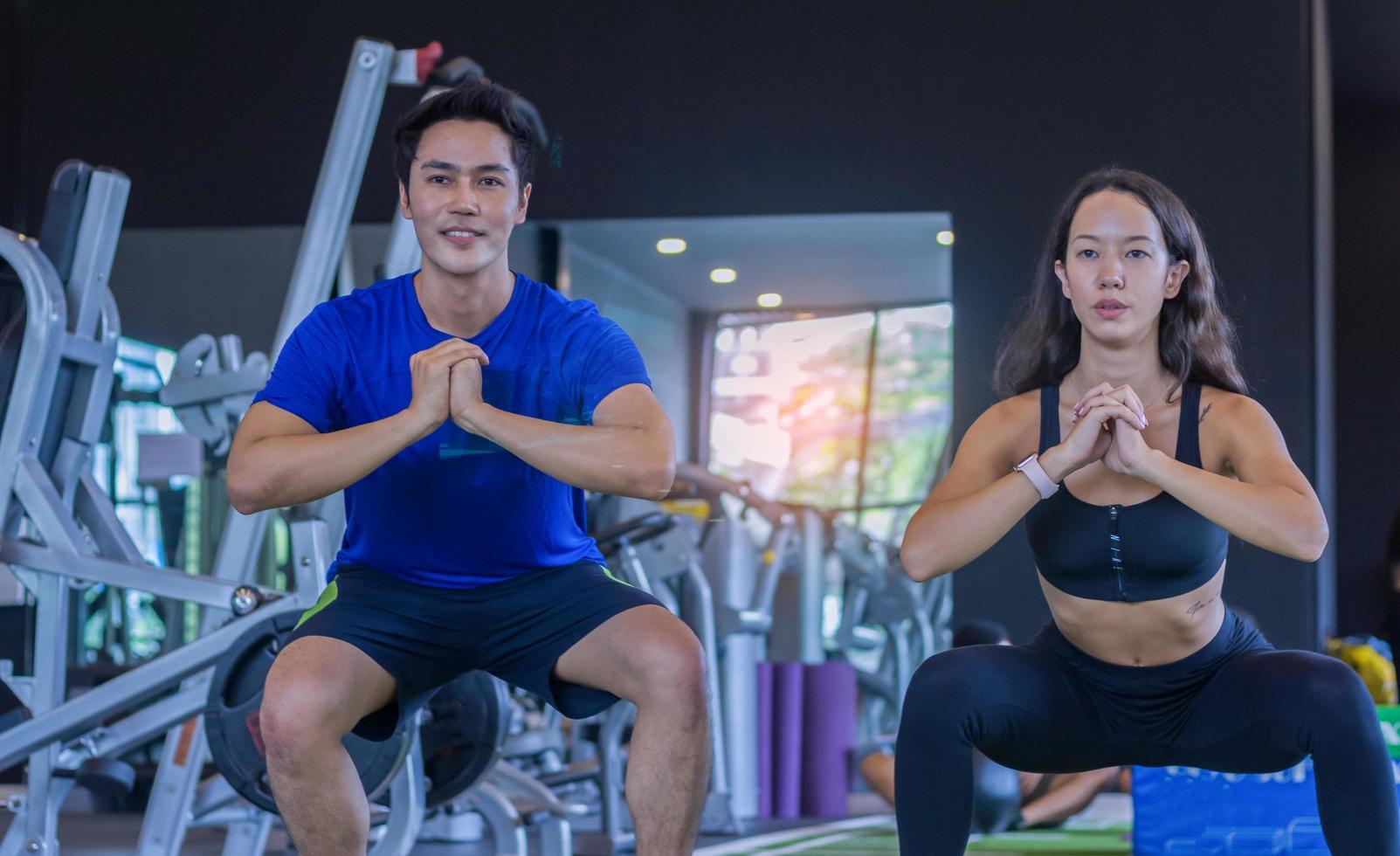 belle femme asiatique fait de l'exercice dans une salle de sport avec un entraîneur personnel fitness bel homme photo