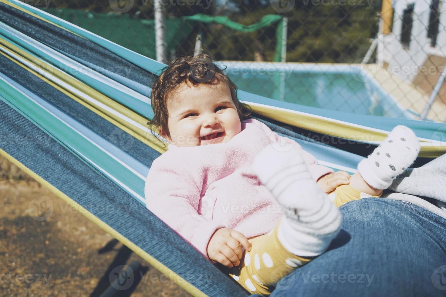 petit bébé s'amusant sur un hamac par une journée ensoleillée photo