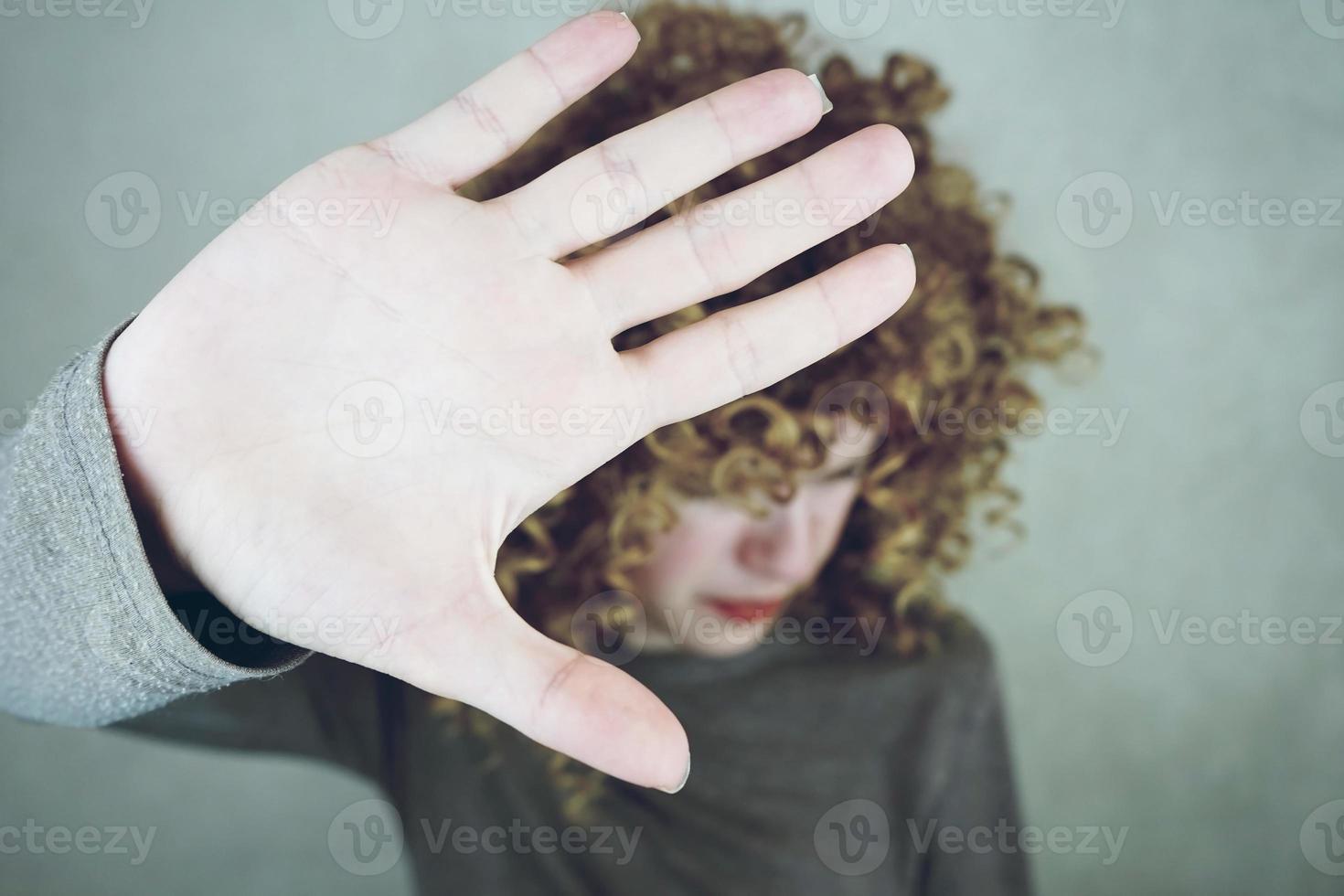 gros plan sur la paume de la main d'une belle et jeune femme qui couvre son visage ses cheveux sont bouclés et blonds elle a l'air en colère ou fatiguée photo