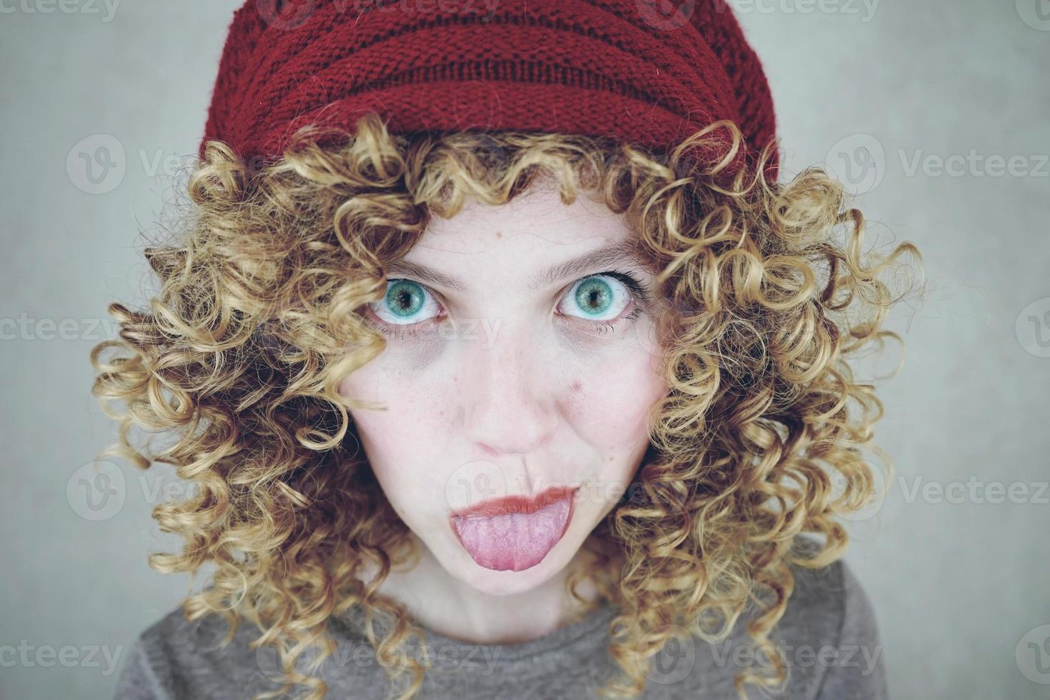 Portrait en gros plan d'une belle et drôle jeune femme aux yeux bleus et aux cheveux blonds bouclés tirant la langue portant un bonnet de laine rouge photo