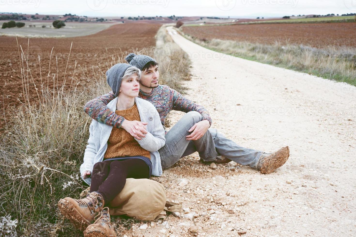 couple de jeunes millénaires s'embrassant et se reposant près d'un sac à dos lors d'un voyage d'aventure sur un chemin de campagne en plein air photo