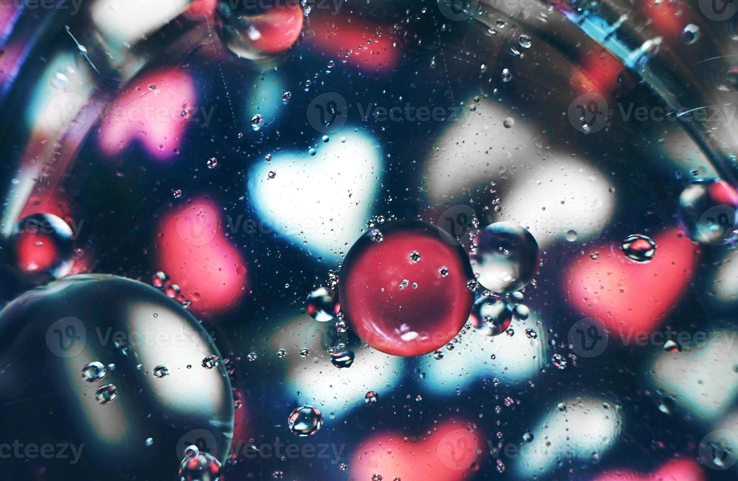 une belle et vibrante macro de bulles d'huile sur l'eau avec un motif flou de coeurs blancs et roses sur fond noir photo