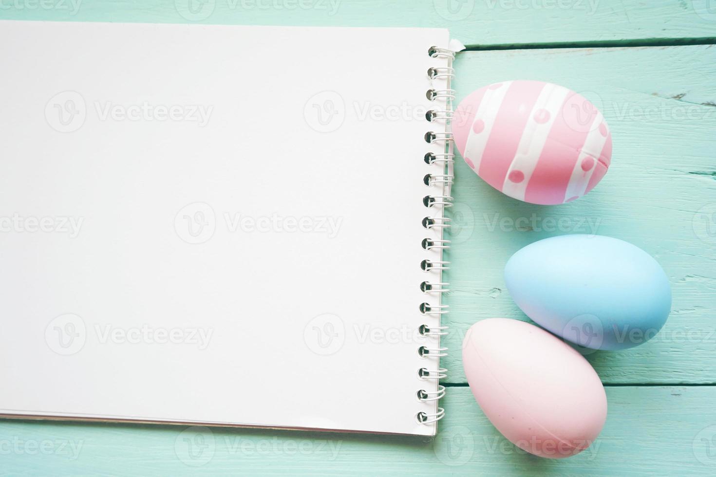 un beau gros plan coloré d'œufs de pâques isolés dans des couleurs unies et rayé par un cahier sur une table en bois bleu pastel avec de l'espace photo