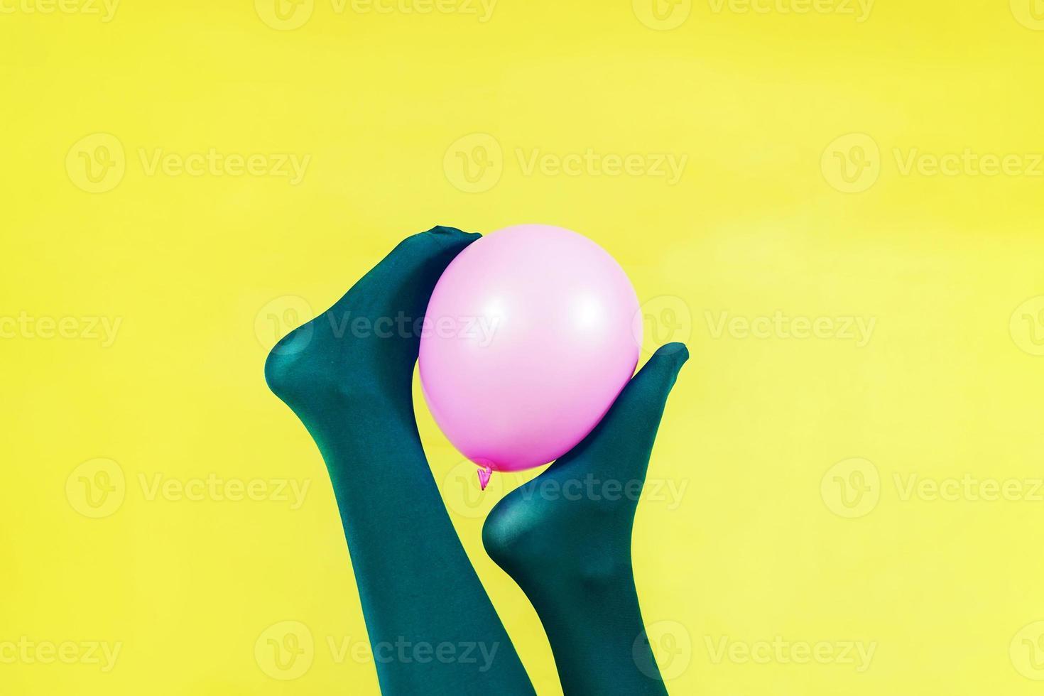 jambes vertes d'une femme tenant un ballon rose contre un mur jaune photo