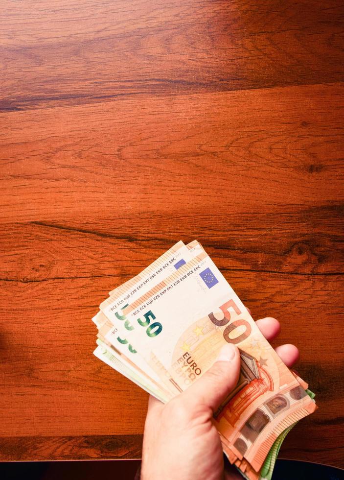 main tient pile de cinquante billets en euros fond de table en bois. salaires et salaire minimum dans l'union européenne. photo