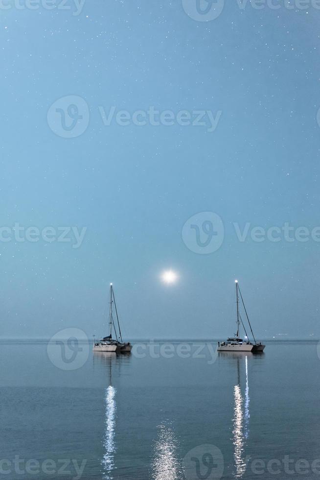 deux bateaux au clair de lune. deux navires ancrés en pleine mer au clair de lune, péninsule de kassandra, grèce. photo