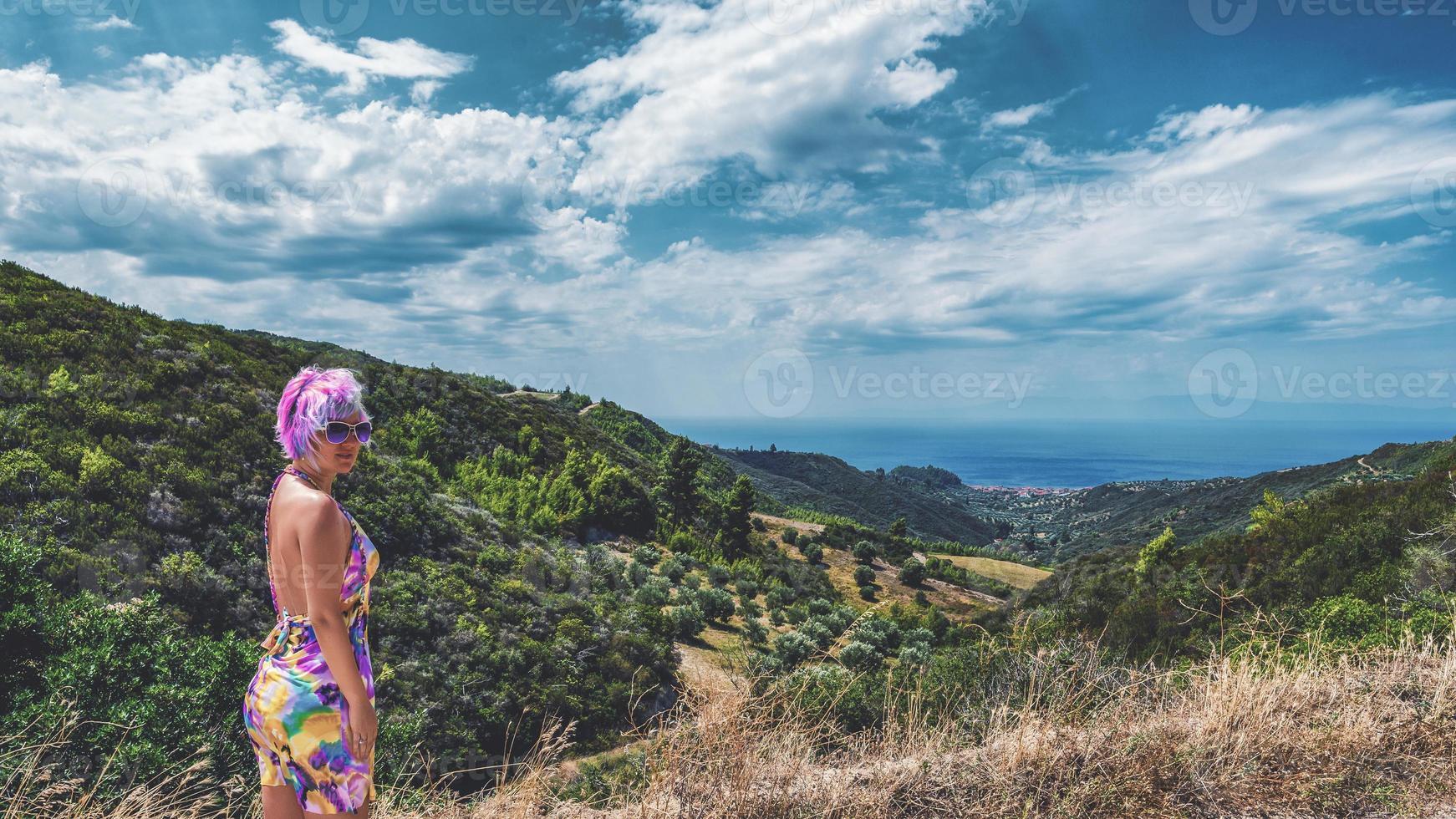 femme aux cheveux roses fous. femme aux cheveux roses regardant la caméra, à l'horizon, nous voyons une petite ville nea skioni depuis l'un des points les plus élevés de la péninsule de kassandra, en grèce. photo