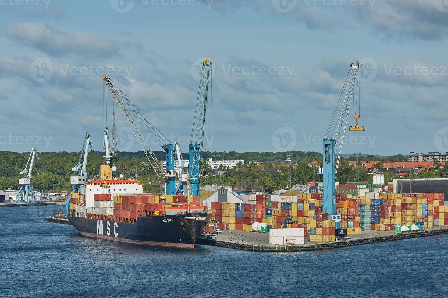 Une grue portuaire charge un conteneur à Fredericia, Danemark photo