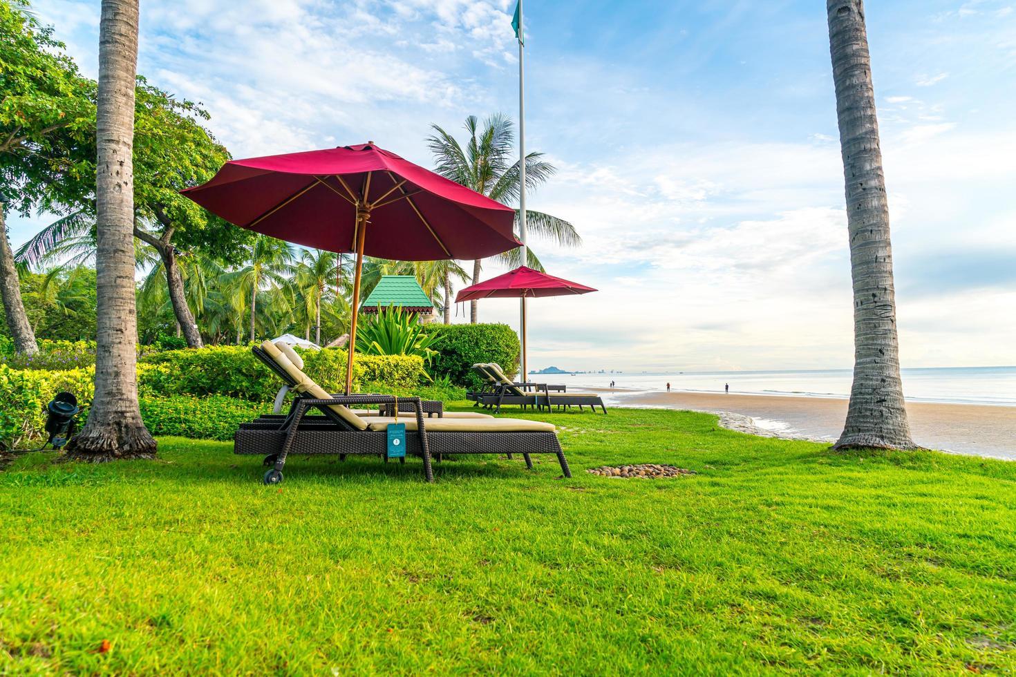 parapluie avec chaise avec fond de plage de mer et lever de soleil le matin photo