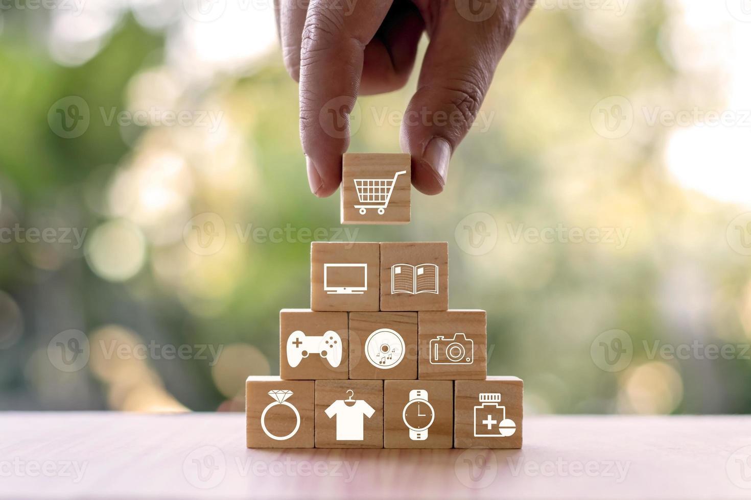 une jeune femme sélectionne une icône de panier d'achat et une icône de panier d'achat sur un blog en bois, une idée d'entreprise en ligne et un guide pour faire des choix de consommation intelligents et sûrs. photo