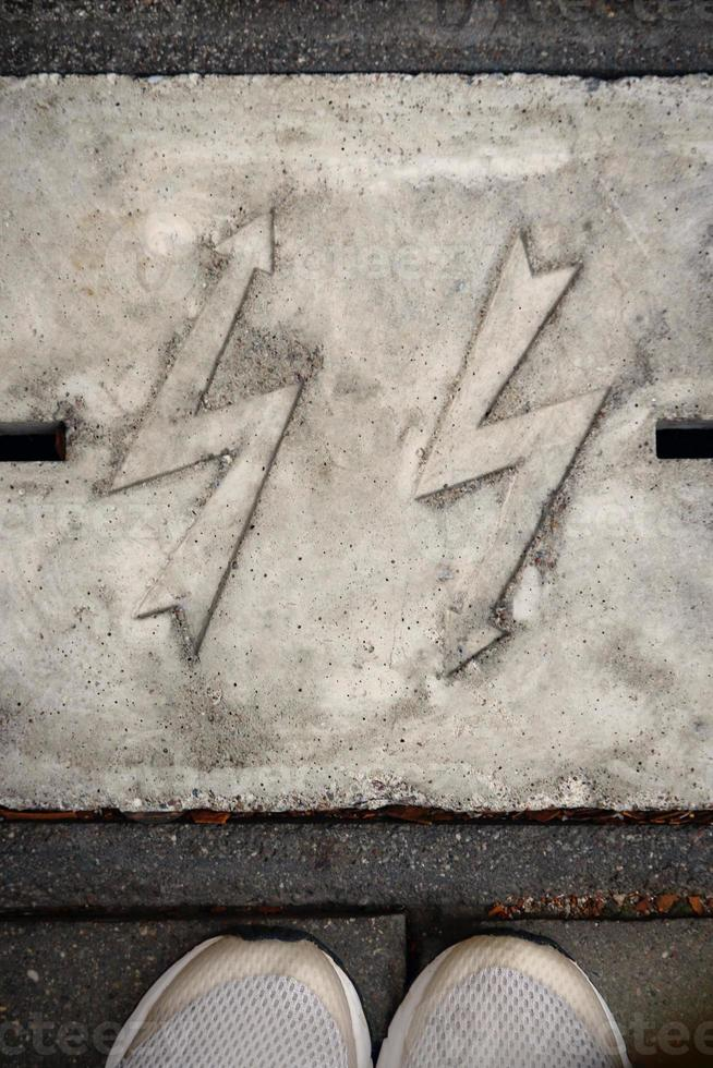 foudre en zigzag en relief dans le béton gris avec des pieds visibles debout sur la chaussée photo