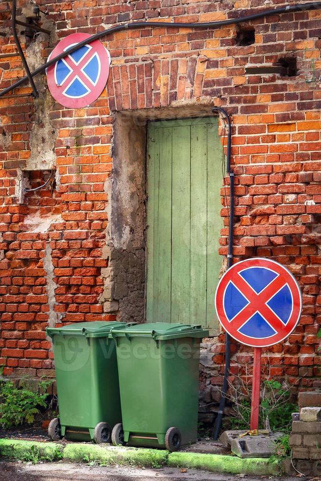 deux poubelles debout sur rue avec mur de brique rouge avec porte en bois verte et deux panneaux de signalisation restrictifs photo