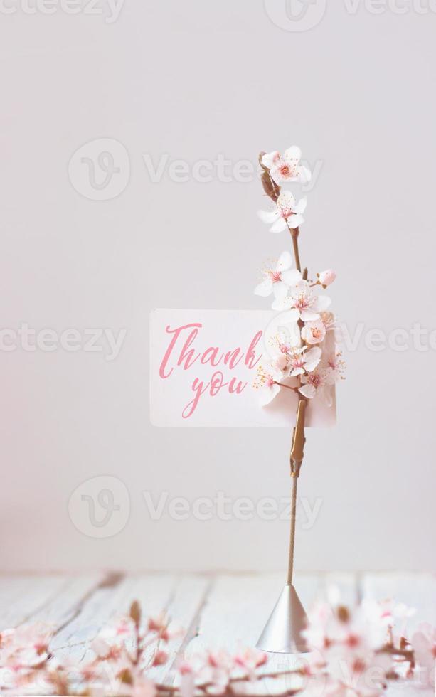 Fleurs de cerisier sauvage et porte-notes avec note de remerciement, sur fond de bois blanc photo