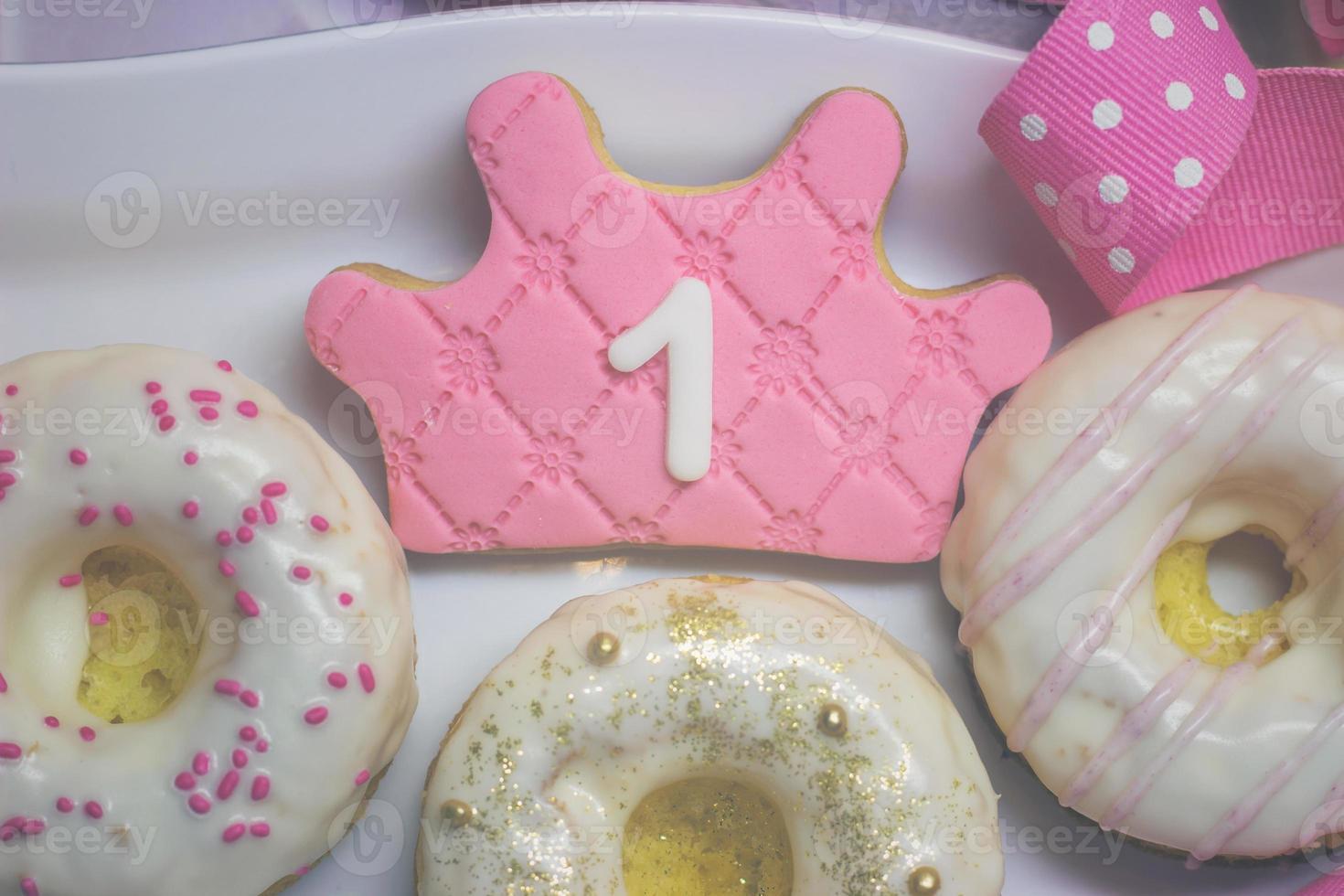 biscuits du premier anniversaire - biscuit en forme de couronne de glaçage royal et beignets décorés photo