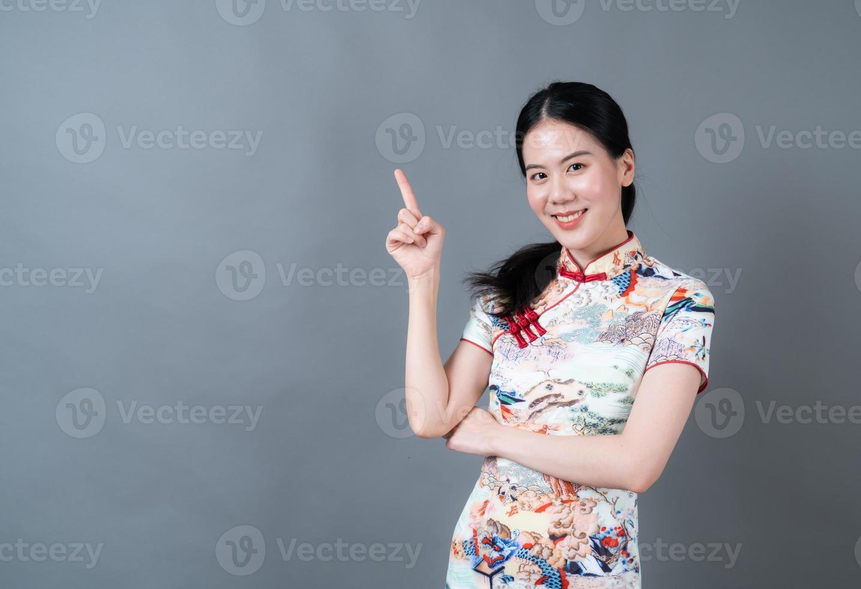 belle jeune femme asiatique porter une robe traditionnelle chinoise avec la main présentant sur le côté photo