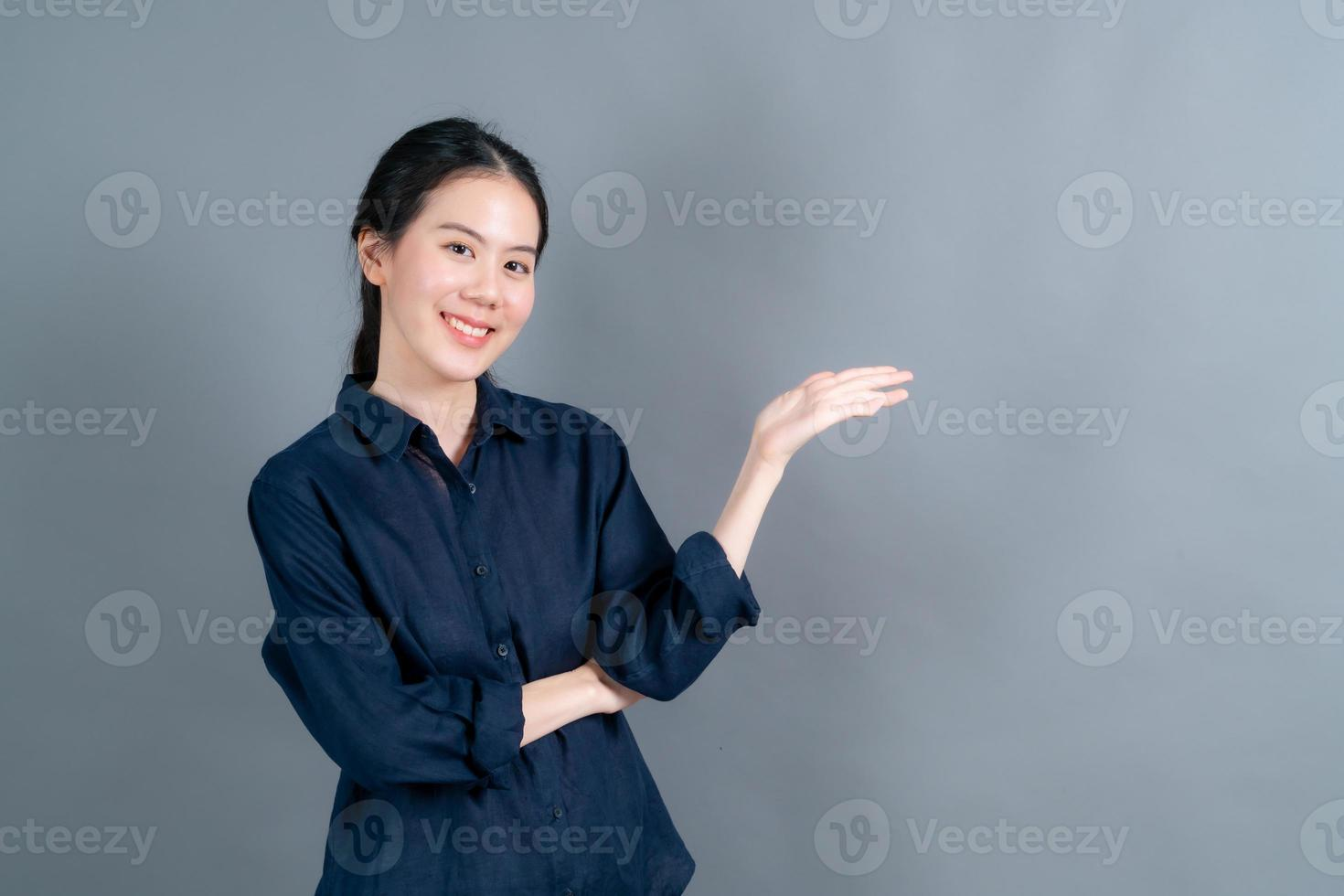 femme asiatique avec la main présentant sur le côté photo