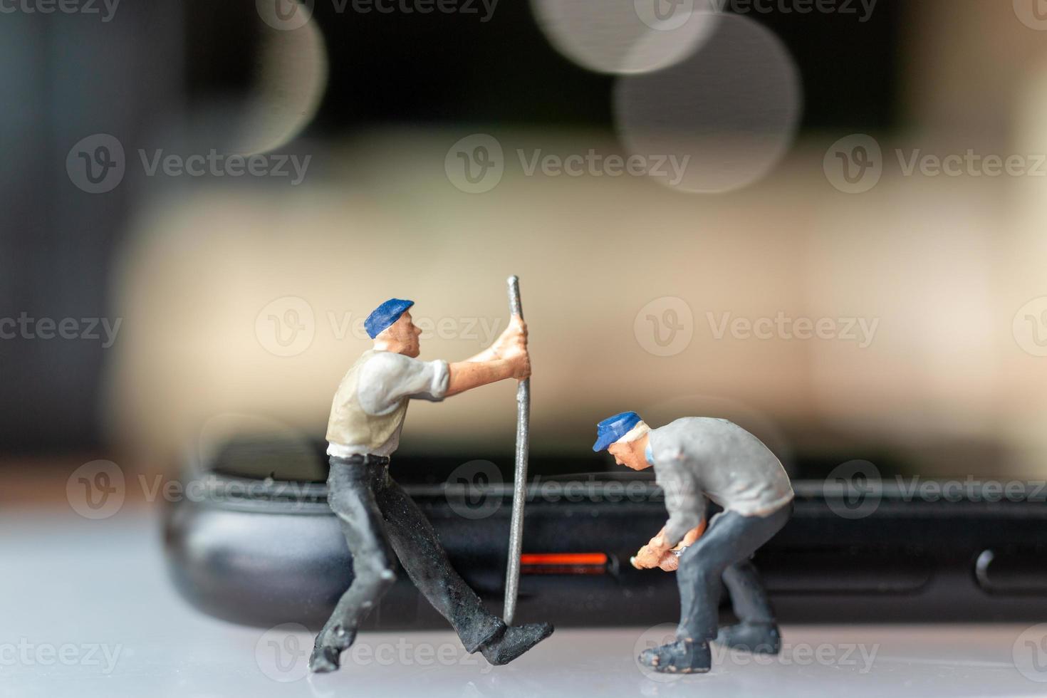 travailleur miniature avec des outils réparant un téléphone portable photo