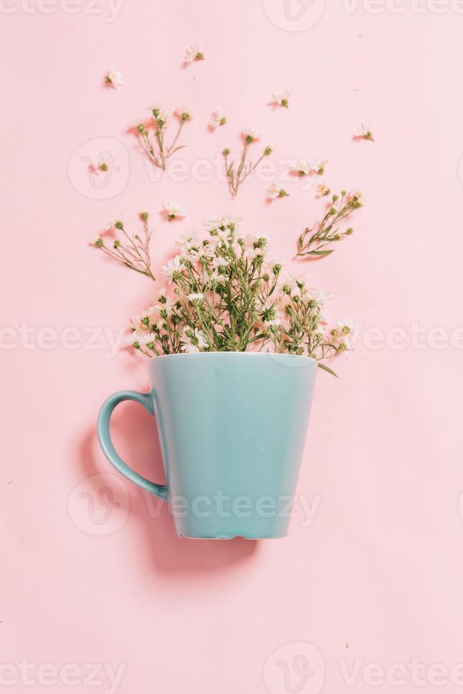 chrysanthèmes dans une tasse bleue sur fond rose photo