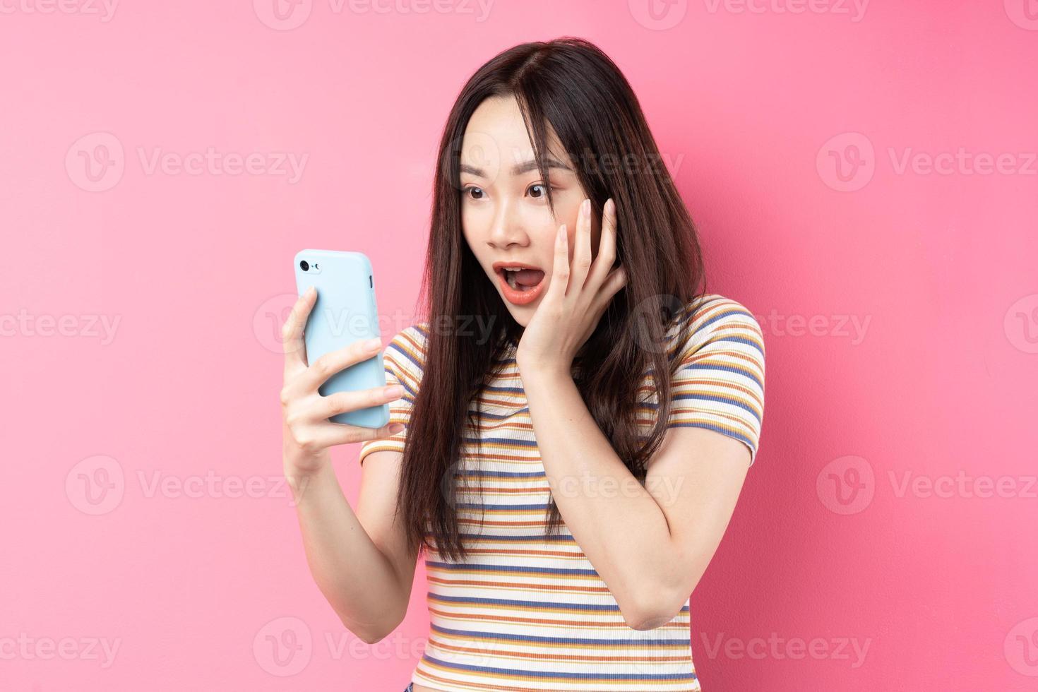 jeune femme asiatique utilisant un smartphone sur fond rose photo