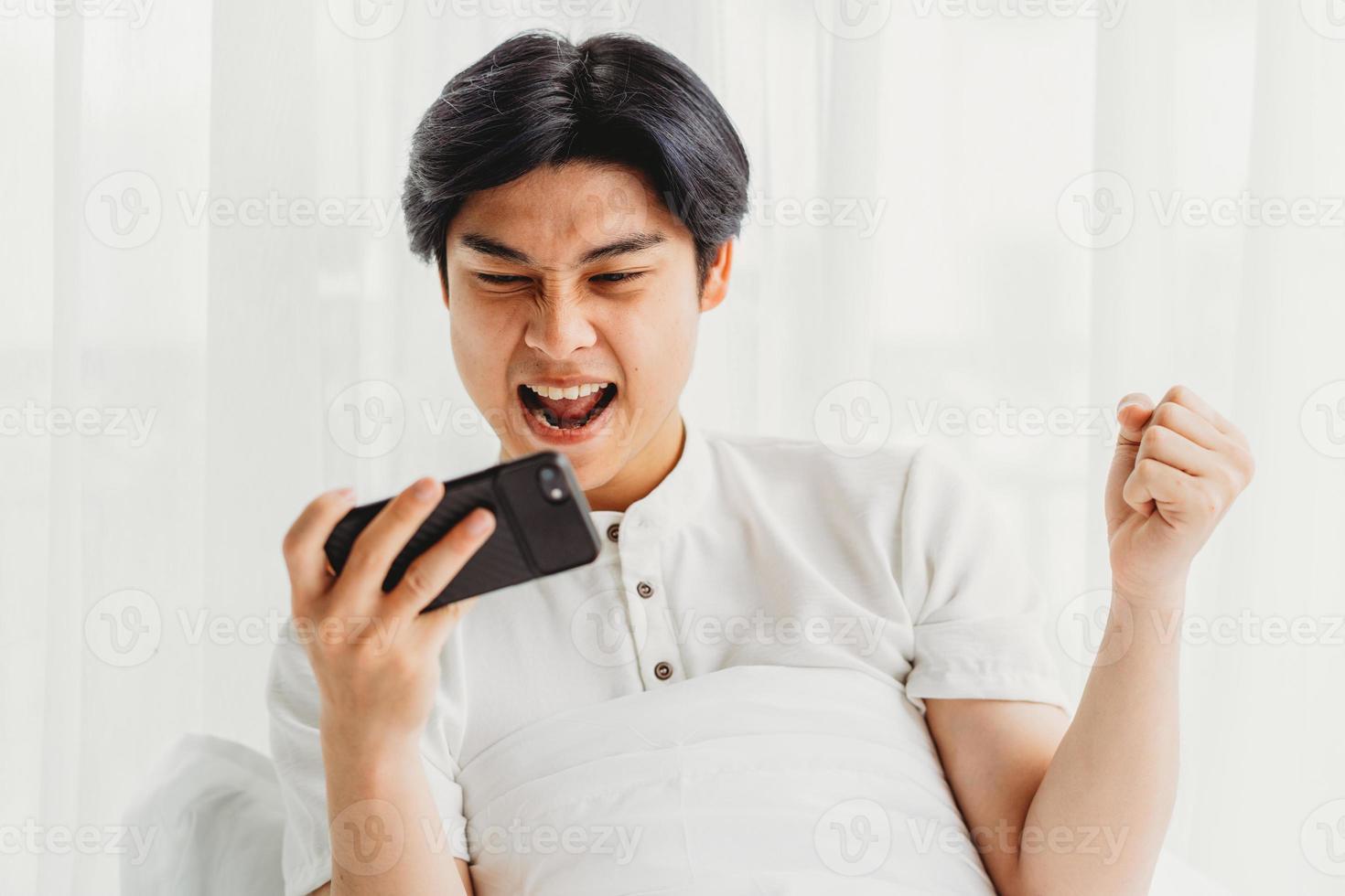 homme asiatique assis dans son lit jouant au jeu. l'homme asiatique est excité par la victoire en jouant au jeu mobile photo