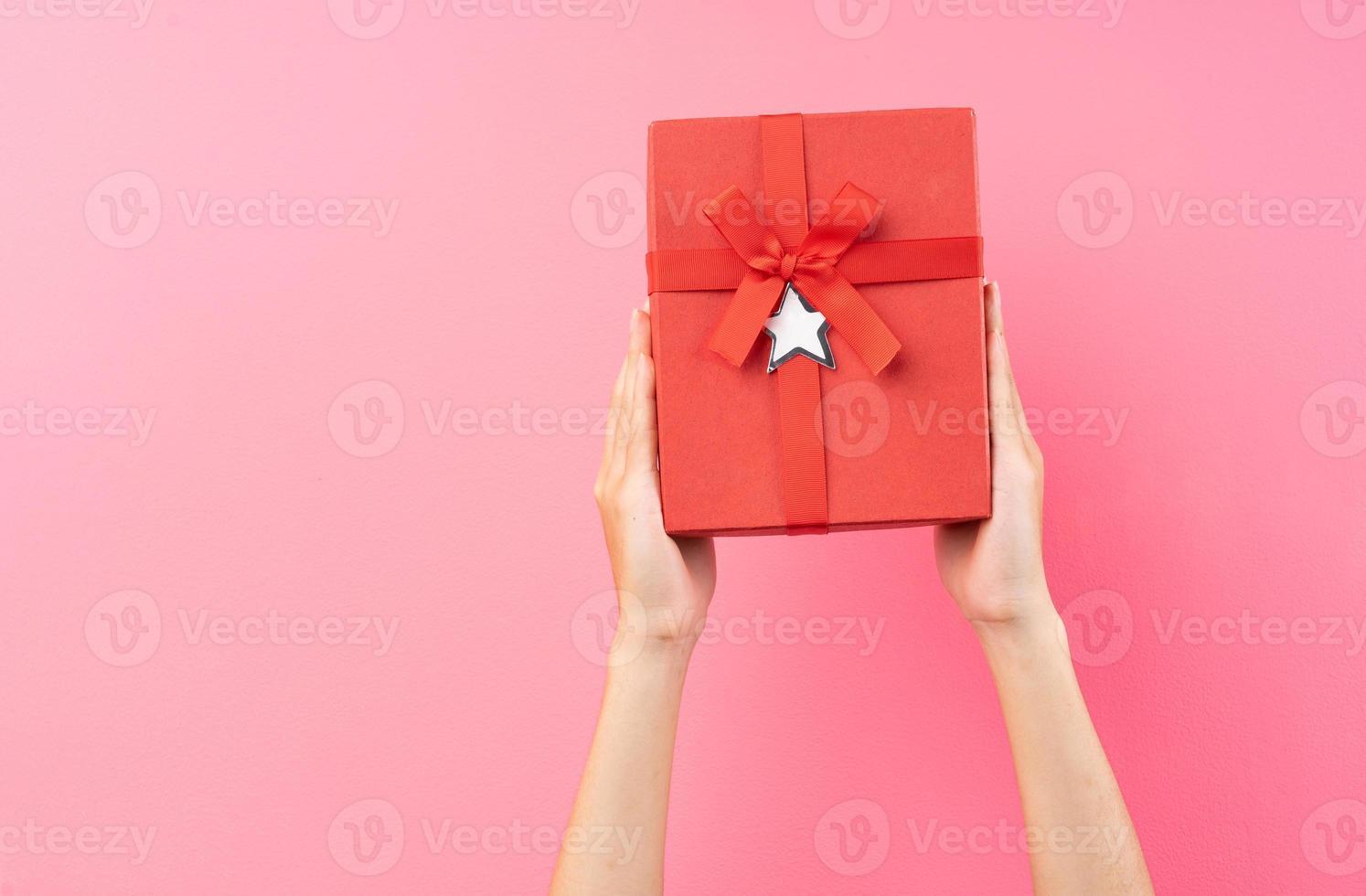 mains tenant une boîte cadeau rouge sur fond rose photo