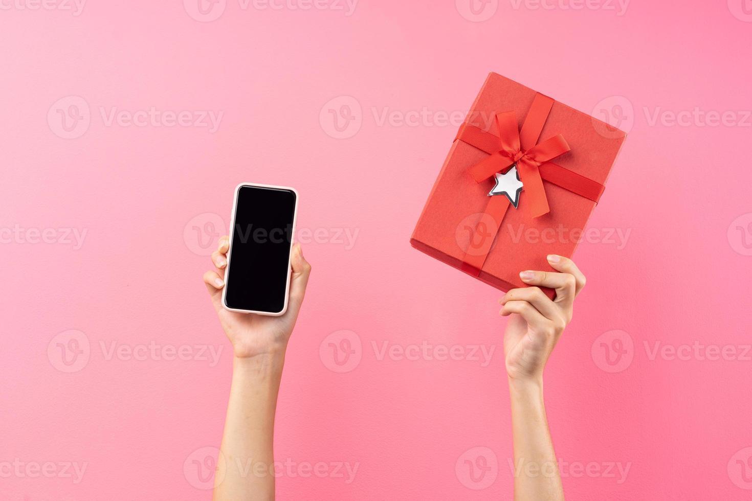 mains tenant une boîte cadeau rouge et un téléphone photo